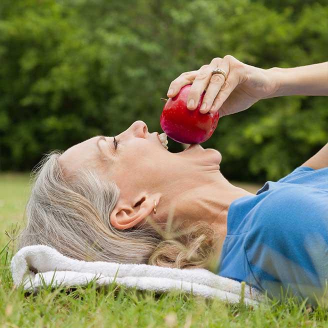 Žena si odhryzuje z jablka | Protefix
